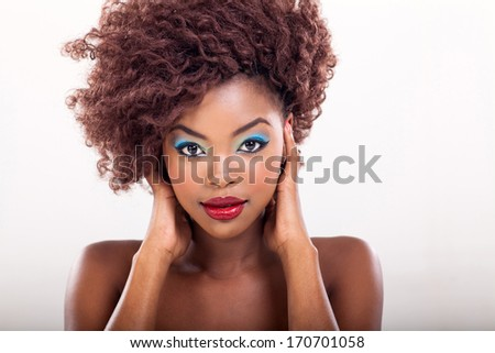 attractive young african american woman with makeup on plain background