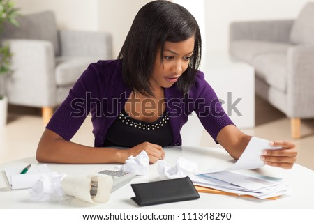 Attractive young African American woman working on finances at home wearing purple jacket sitting at dining table. - stock photo