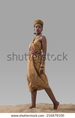 Attractive young African fashion model standing on sand on gray studio background