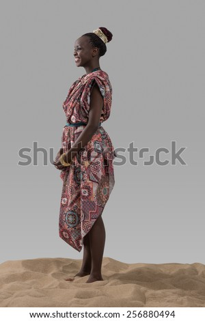 Attractive young African fashion model standing on sand on gray studio background - stock photo