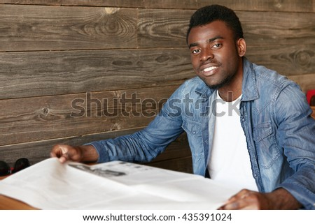 Attractive young African office worker in denim jacket reading tabloid while sitting at the wooden table at a restaurant during lunch break. Handsome black student relaxing at a student cafe - stock photo