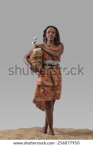 Attractive young african woman carrying basket with cotton and goods on sand on gray studio background - stock photo