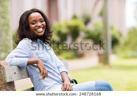 attractive young african woman sitting on a bench outdoors - stock photo