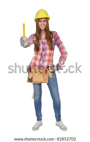 Attractive young artisan with a tool holding a yellow ruler - stock photo