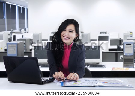 Attractive young asian businesswoman with beautiful face, smiling at the camera in the office - stock photo