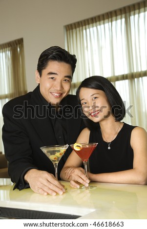 Attractive young Asian couple smiling towards the camera and holding cocktails at a bar. Vertical shot. - stock photo
