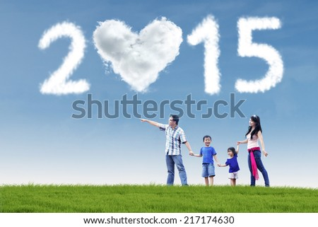Attractive young asian family walking in field and holding hands under cloud of 2015 - stock photo
