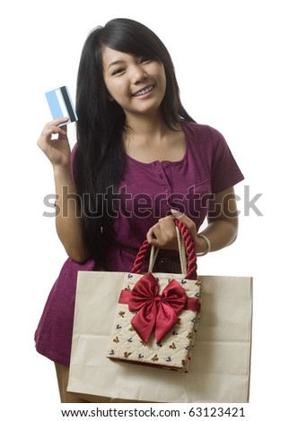 Attractive young Asian girl with shopping bags and credit card - stock photo