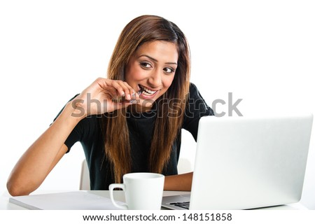Attractive young Asian Indian teenage woman, studying with a non-branded generic laptop in an office while chewing on a pen - stock photo
