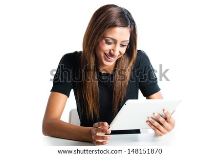 Attractive young Asian Indian teenage woman, working with a non-branded generic portable tablet  - stock photo