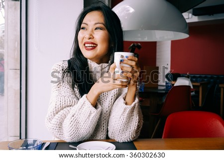 Attractive young Asian student drinking coffee during her lunch break.Portrait of young gorgeous female drinking tea and looking with smile out of the coffee shop window - stock photo