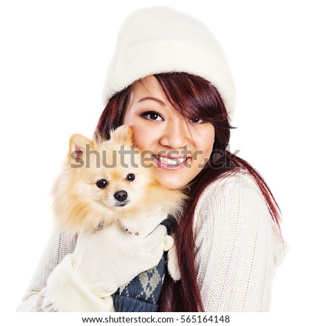 Attractive young Asian woman in a soft white sweater and knit cap, holding a small dog.