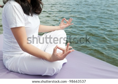 Attractive young asian woman practicing yoga meditation at sunrise by the ocean - stock photo