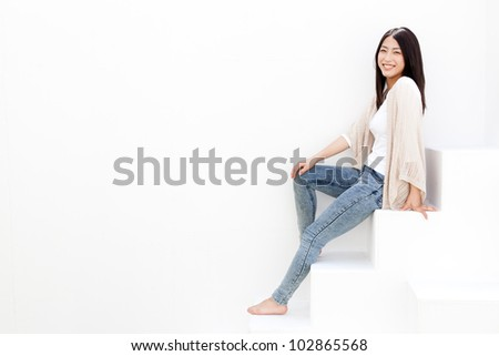 attractive young asian woman sitting isolated on white background - stock photo