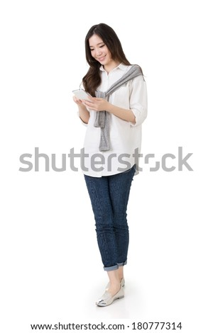 Attractive young Asian woman using cellphone to check message, full length portrait isolated on white background. - stock photo