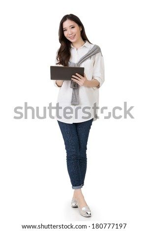 Attractive young Asian woman using pad, full length portrait isolated on white background.
