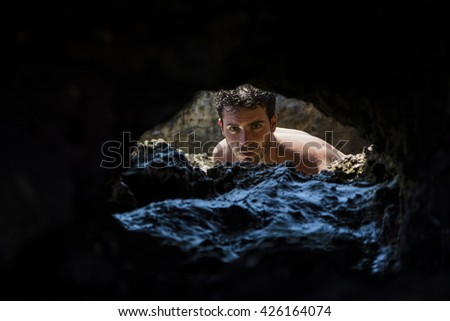 Attractive young athletic man in the sea or ocean by the rocky shore, showing naked muscular torso, serious expression - stock photo