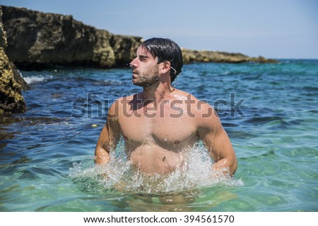 Attractive young athletic man in the sea or ocean jumping up out of water, showing naked muscular torso - stock photo