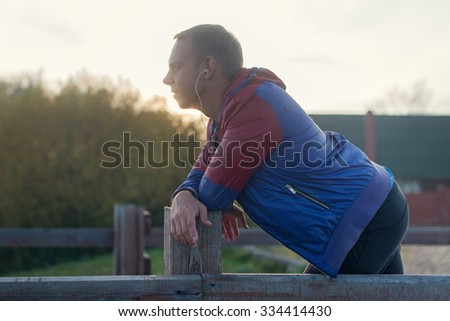 Attractive young athletic man standing on the beach and looks into the distance of the river to the bridge, listening to music - stock photo