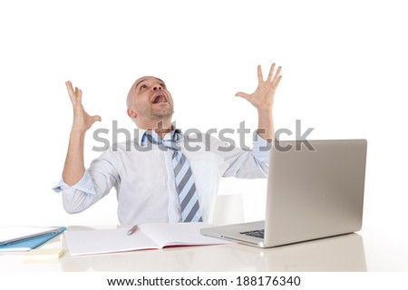 attractive young bald business man screaming in crisis , stress and frustration at computer from pressure watching stocks crash , money and sales loss or technical problems at the office desk - stock photo