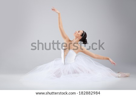 attractive young ballet dancer acting out. beautiful ballerina sitting forward split - stock photo