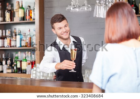 Attractive young barman is holding cocktail and giving glass to woman. He is looking at her with joy and smiling. The man is standing and posing - stock photo