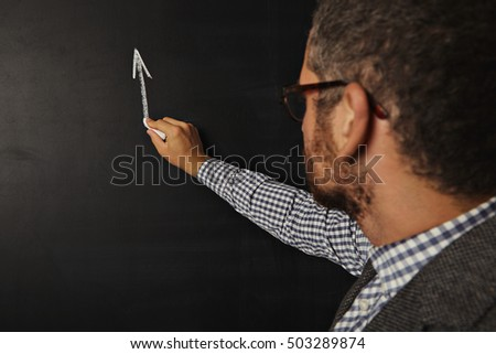 Attractive young bearded teacher starting to draw a graph on the blackboard