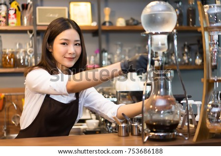 Attractive young beautiful caucasian barista make iced slow drip coffe working Order Concept and smiling look at camera.