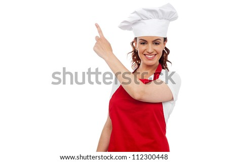 Attractive young beautiful woman chef wearing red apron and toque pointing at copy space - stock photo