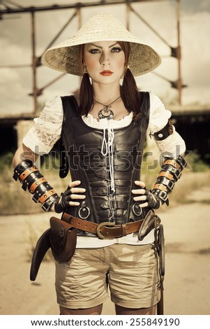 Attractive young beautiful woman in leather corset posing on the industrial background. - stock photo