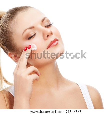 Attractive young beautiful woman looking out of camera and applying cream on white background - stock photo