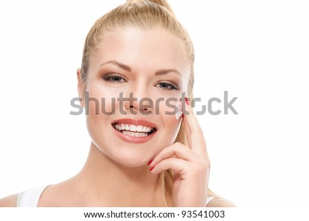 Attractive young beautiful woman looking to the camera and applying cream on white background