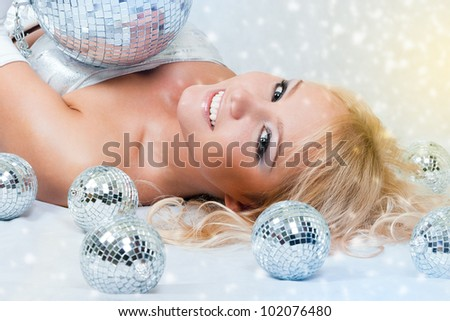 Attractive young beautiful woman lying down on floor with disco balls - stock photo