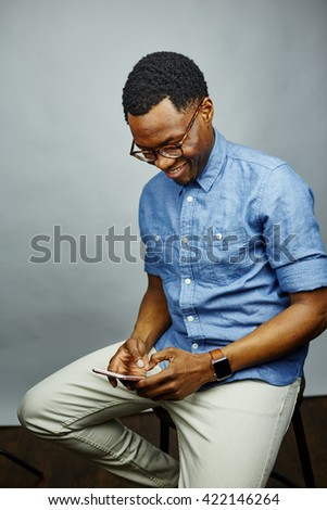 attractive young black male studio holding smart phone looking at phone - stock photo