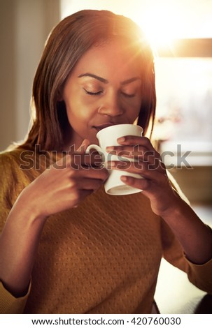 Attractive young black woman drinking a cup of freshly brewed coffee smelling the aroma with her eyes closed in bliss as she relaxes indoors at home - stock photo