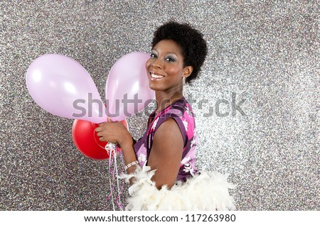 Attractive young black woman holding pink and red balloons against a silver glitter background, smiling. - stock photo
