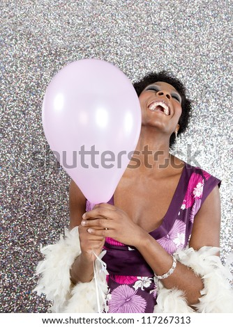 Attractive young black woman holding pink balloons against a silver glitter background, laughing.