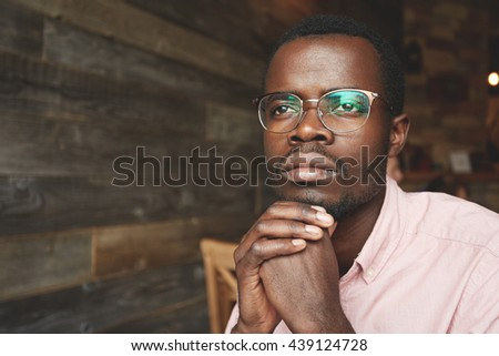 Attractive young black writer in pink shirt, sitting at a cafe with dreaming face expression, looking through the window, gaining inspiration in urban landscape outside, reflected on his oval glasses - stock photo