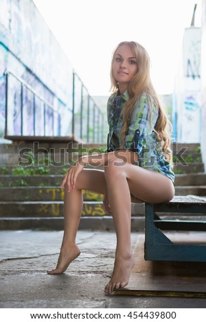 Attractive young blond barefoot woman posing outdoors - stock photo