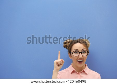 Attractive young blond girl against blue wall. - stock photo