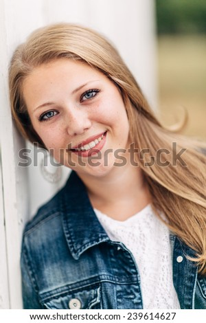 Attractive Young Blond leaning against white wall, looking at camera, smiling, jean jacket