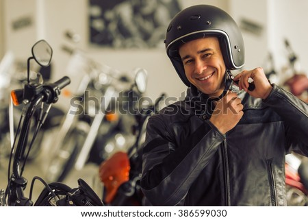 Attractive young blond man in black leather jacket is looking at camera, adjusting his helmet and smiling while standing in a motorbike salon - stock photo