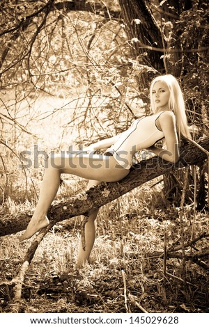 Attractive young blond model sitting on a tree - stock photo