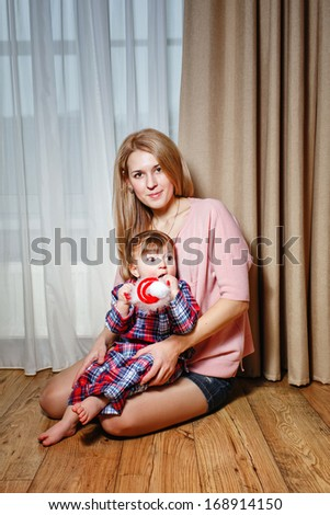 Attractive young blond mother holding her baby in her arms - stock photo
