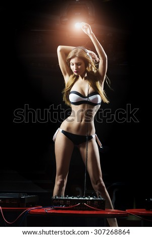 Attractive young blond sexy dj girl in lingerie and headphones with long hair and straight body dancing at red table with mixer console in night club on dark with light sparkle background