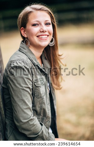 Attractive Young Blond Woman in front of horse stable leaning against wall, laughing - stock photo