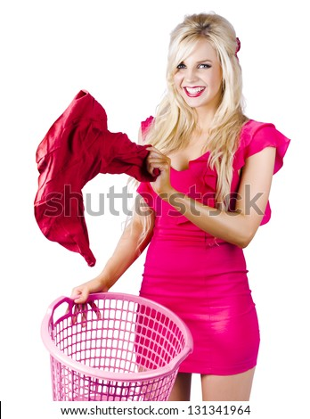 Attractive young blond woman in pink dress putting laundry in basket, white background - stock photo