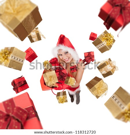 Attractive young blond woman in santa costume throwing christmas gifts. Studio shot, isolated on white background. Upper gifts are blurred to create motion effect - stock photo