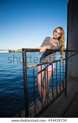 Attractive young blond woman in striped blouse and jeans shorts posing behind iron fence near the river - stock photo