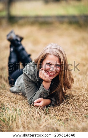 Attractive Young Blond Woman laying in straw feet up laughing, hand on chin - stock photo